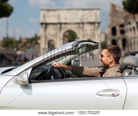travel, tourism, road trip, transport and people concept - happy man driving cabriolet car over triumphal arch in city of rome background