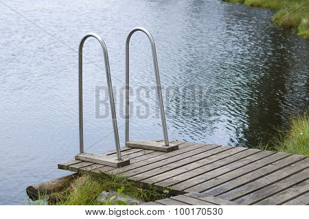 Small Wooden Jetty With Stairs To The Pond