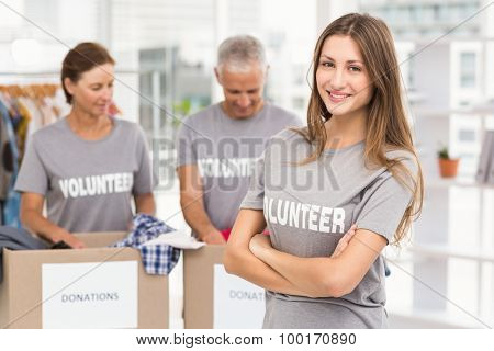 Portrait of smiling female volunteer with arms crossed in the office