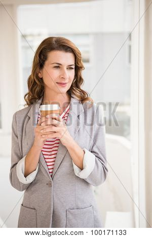 Casual businesswoman holding take-away cup in the office