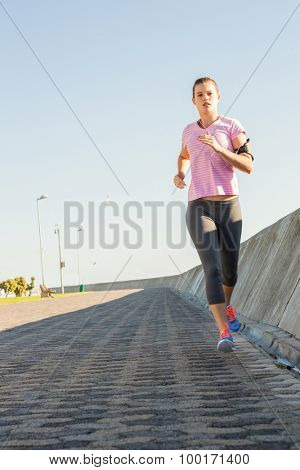 Focused sporty blonde jogging at promenade on a sunny day