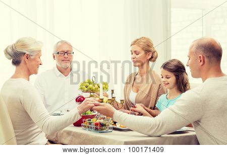 family, holidays, generation and people concept - smiling family having dinner and praying at home