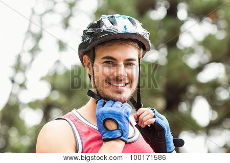 Handsome young biker looking at camera in the nature