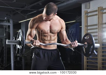 Handsome Muscular Male Model In A Standing Position With Perfect Body Doing Biceps Exercise