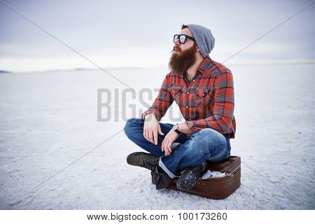 bearded hipster alone in the salt flats looking out in deep thought with copyspace composition