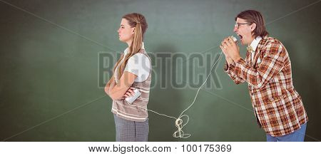 Geeky hipsters using string phone against green chalkboard