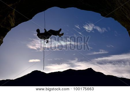 Silhouette Of Rock Climber Over Blue Sky Background