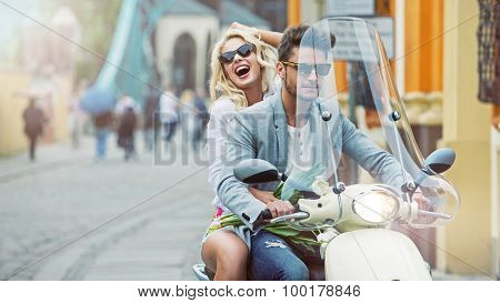 Happy fashionable couple riding on scooter