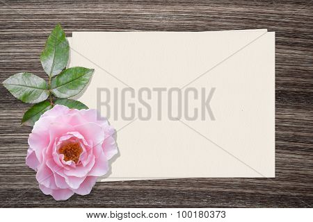 Pink rose and and paper on wood background