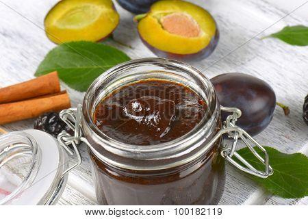 close up of fresh plum jam, fresh plums and cinnamon sticks
