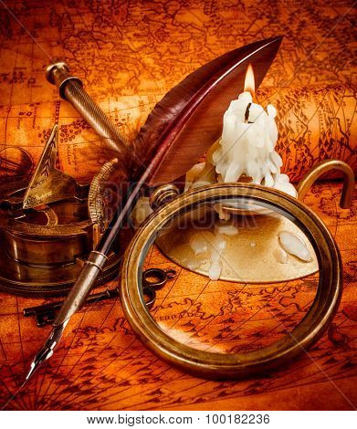 Vintage compass, magnifying glass, quill pen, spyglass lie on an old ancient map in 1565 with a lit candle. Vintage still life.