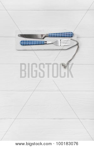 Wooden white background for a menu card with cutlery in blue white checked colors for restaurants and gastronomy placards.