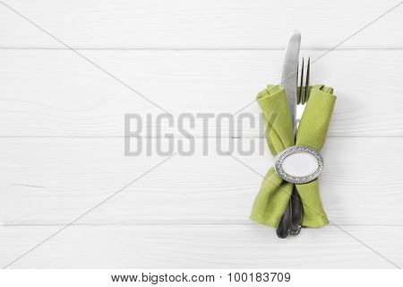 Wooden white background for a menu card with cutlery in apple green color for restaurants and gastronomy placards.