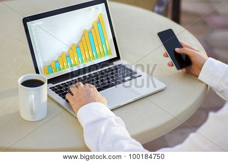 Trader Is Looking At Financial Charts On The Laptop Monitor