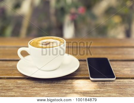 Cup Of Cappuccino And Cell Phone On A Wooden Table