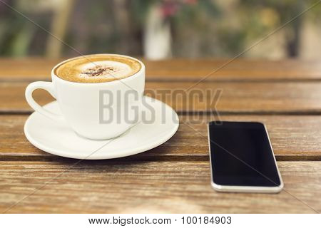 Cup Of Cappuccino And A Cell Phone On A Wooden Table