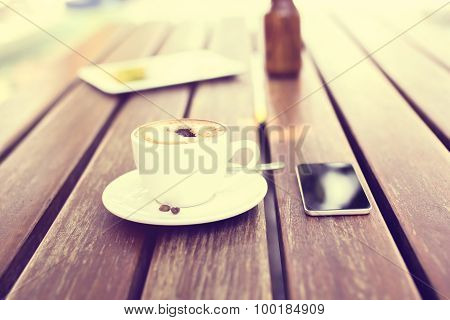 Cappuccino And A Cell Phone On A Table, Vintage Photo Effect