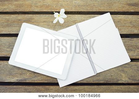 Blank Digital Tablet With Notebook And A Flower On A Wooden Table
