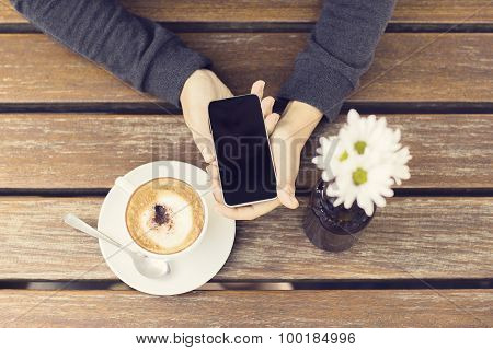 Girl Keeping A Cell Phone And A Cup Of Cappuccino On A Wooden Table