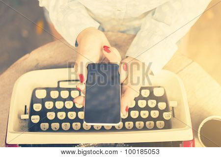 Girl Keeping Cell Phone And A Vintage Typewriter