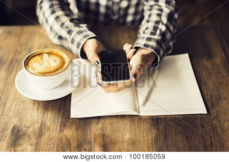 Girl Hands With Cell Phone, Cup Of Coffee And Blank Diary With Pencil On A Wooden Table
