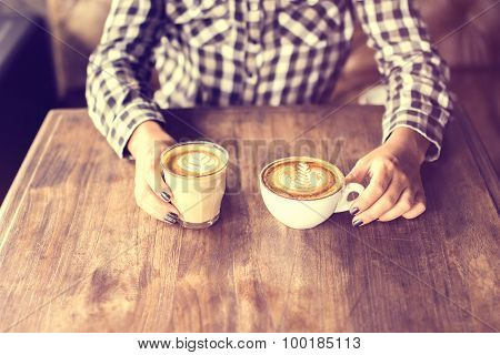 Hipster Girl Holding Two Cups Of Coffee On A Wooden Table
