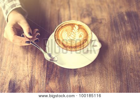 Girl Holding A Teaspoon And Cup Of Cappuccino On A Wooden Table