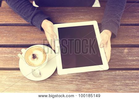 Man Holding Digital Tablet And Cappuccino On A Wooden Table