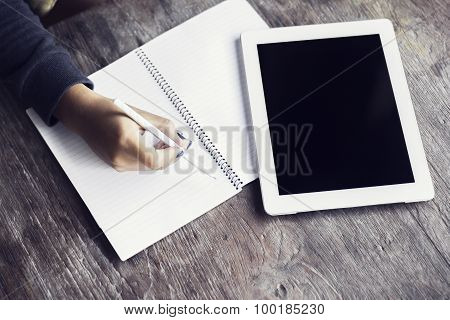 Girl Hand With Pencil, Blank Diary And Digital Tablet On A Wooden Table