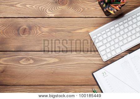 Office desk table with keyboard and calendar notepad. Top view with copy space