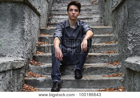 Thoughtful Guy In Gray Clothes Sitting On Gray Stairs