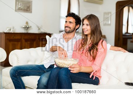 Happy smiling couple watching tv. Shallow depth of field, focus on the woman