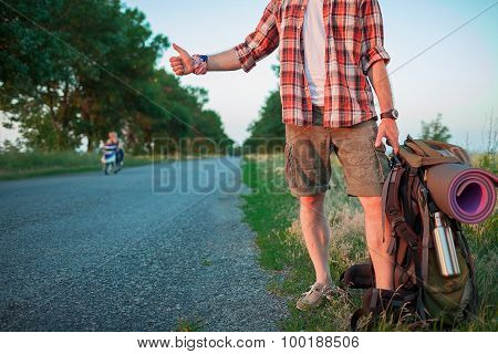 Young caucasian tourist hitchhiking along a road.