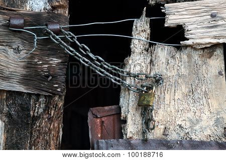 Old And Worn Wooden Closed With Chain And Padlock
