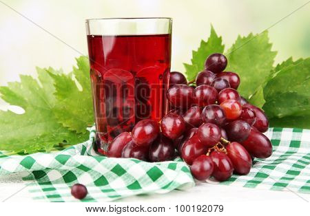 Glass of grape juice on table with checkered napkin on light blurred background