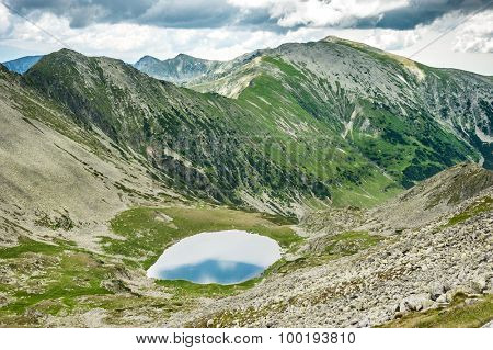Landscape of Retezat National Park mountains in South Carpatians, Transylvania, Romania, Europe. Small lake with blue sky reflection at center, sheep herd near lake.