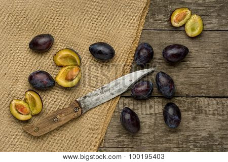 Sweet plums on dark wooden background witth Burlap and knife