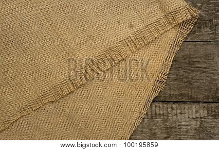 Burlap on rustic wooden background. Top view
