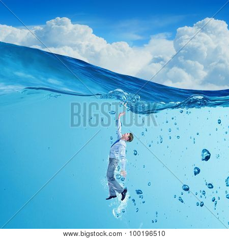 Young businessman in suit swimming in crystal blue water