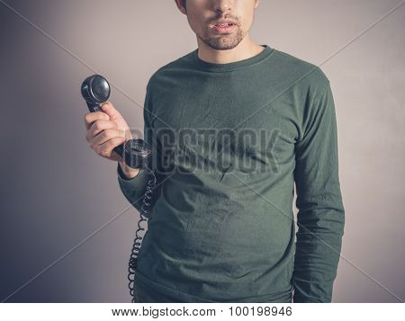 Concerned Young Man Holding Vintage Phone