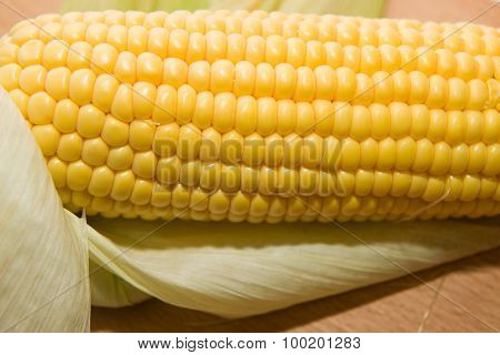 One Ripe Corn On A Wooden Surface