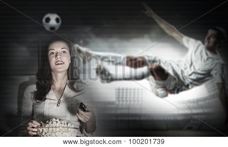 Young girl holding popcorn and watching football match on telly