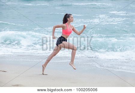 Woman Running On The Beach At Cloudy Morning, Side View