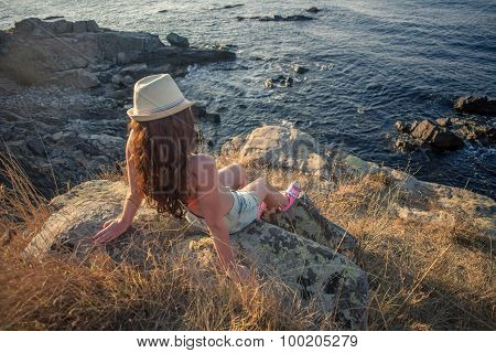 Young Woman Sitting On Rocky Coast And Looking At The Sea