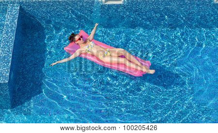 Attractive Woman Swimming On Inflatable Mattress In Pool