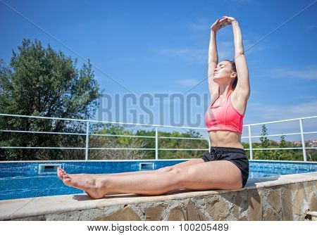 Young Brunette Woman Doing Morning Exercise Near Swimming Pool Outdoor