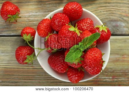 Ripe strawberries in saucer on wooden table, top view