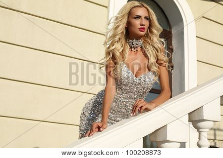 Beautiful Woman With Blond Hair In Luxurious Dress And Bijou