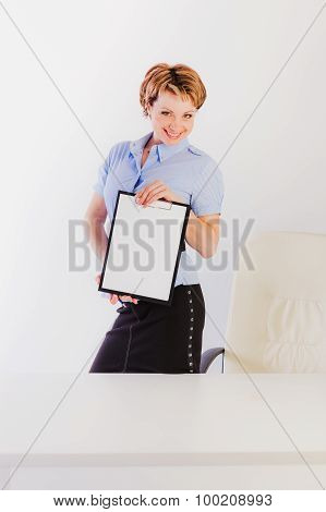 Smiling woman holding clipboard standing nearby desk