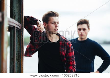 two guys stand in an abandoned building on lake